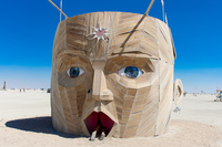 man swallow by giant head Black Rock City,  Nevada,  United States, North America